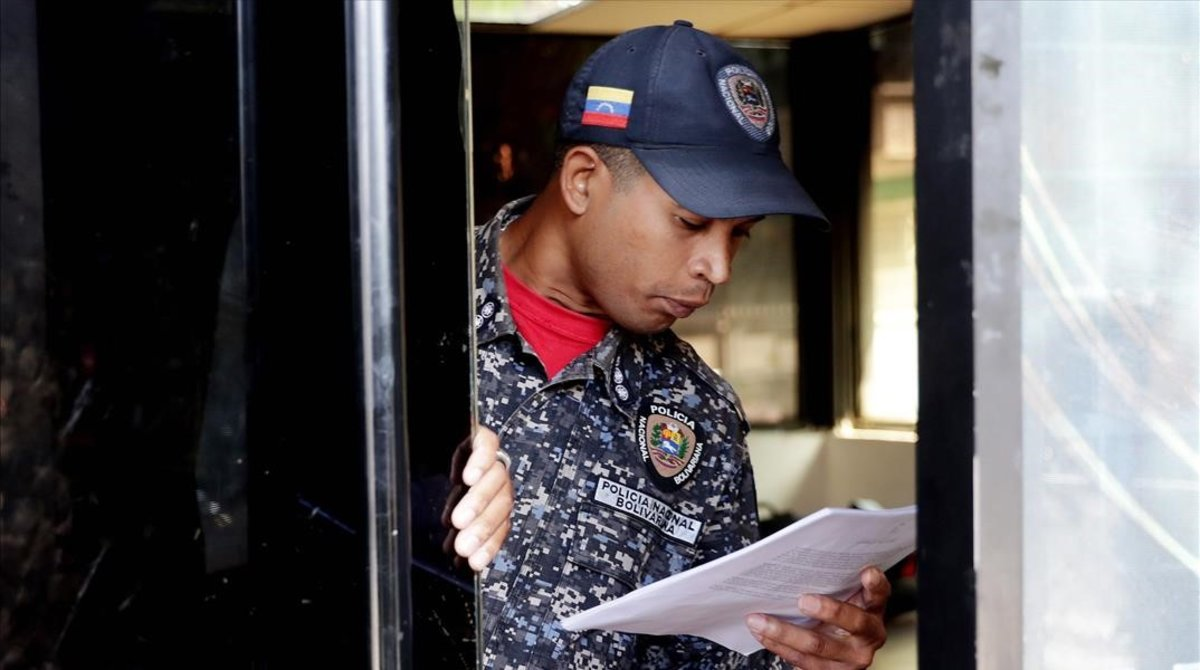 Un polícía de Caracas lee la ley de amnistía distribuida por la oposición.