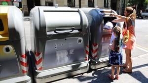 Una mujer tira una bolsa al contenedor de la basura orgánica en Barcelona.