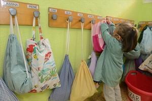 Una niña cuelga su mochila en el CEIP Antoni Gaudí de Cornellà.