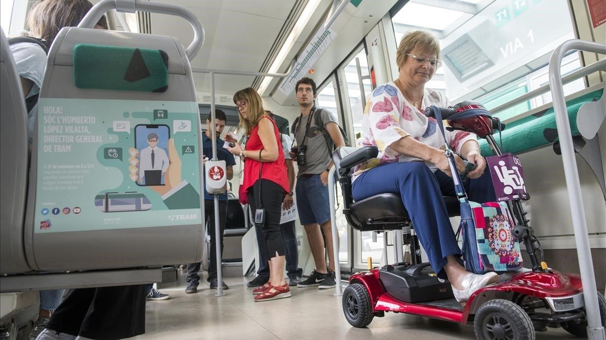 Una usuario del Tram accede al tranvía de Barcelona con su 'scooter', esta mañana