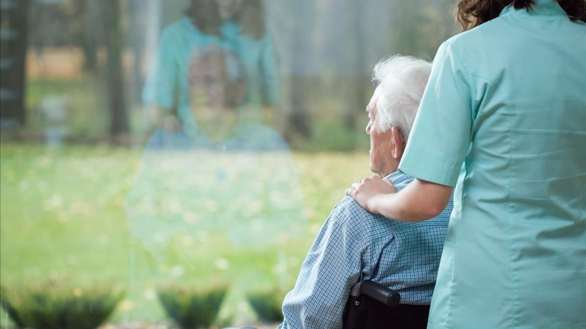 Una enfermera cuida de una anciana.