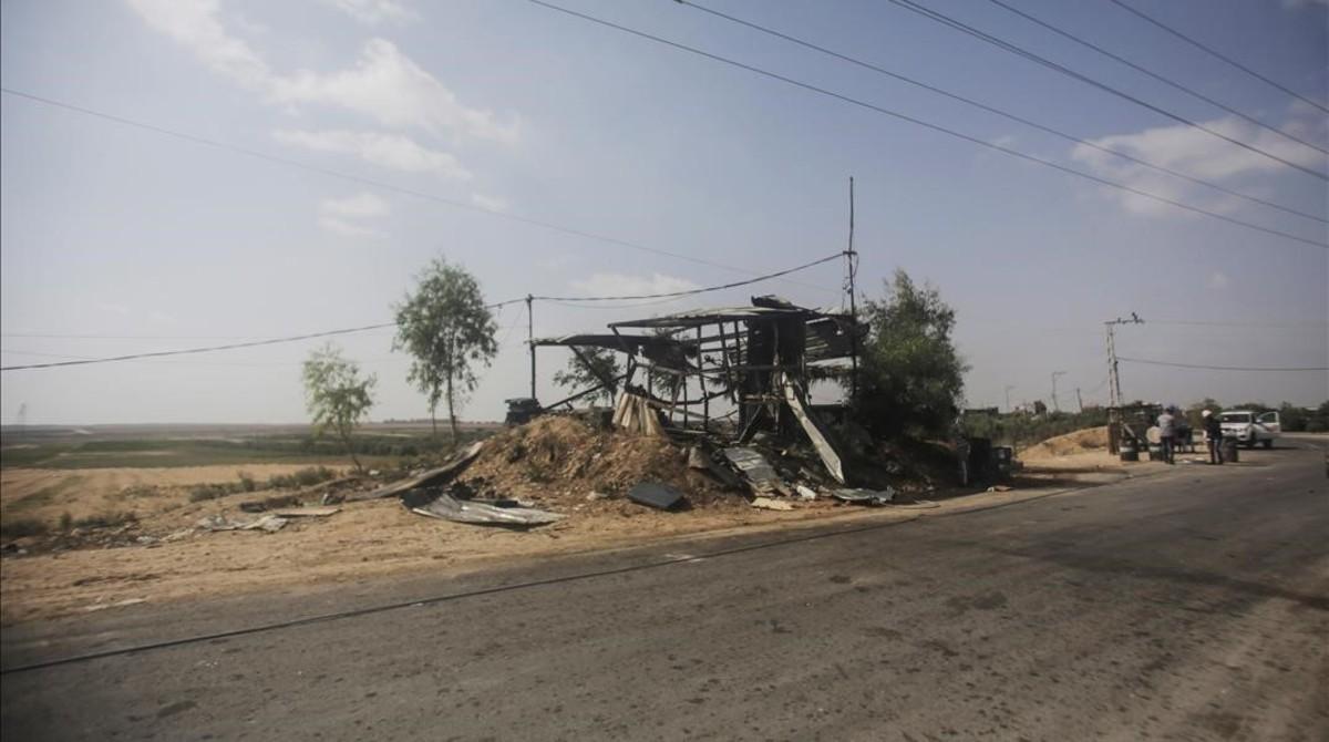 Varios palestinos observan un puesto militar destrozado cerca de la frontera con Israel.