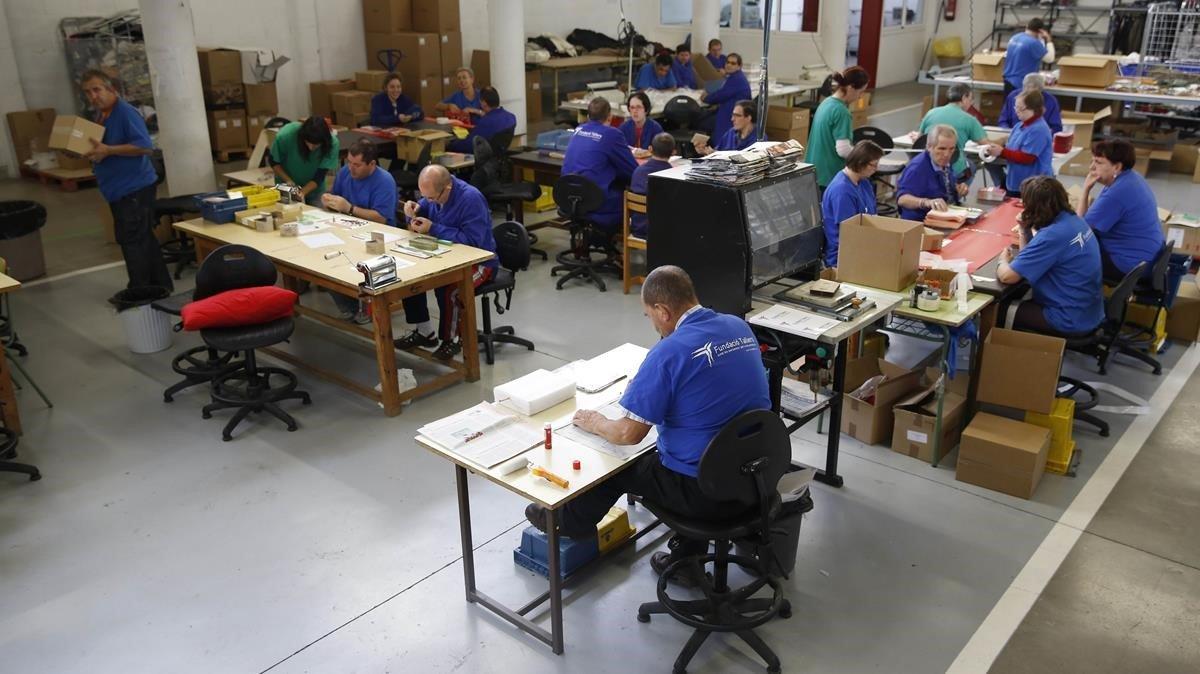 Trabajadores durante su jornada laboral en un centro especial para la inserción de personas con discapacidad.