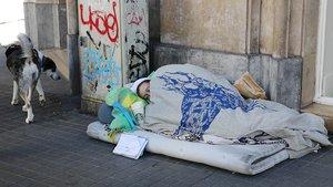 Una mujer sin techo, tumbada a la intemperie en una callle de Barcelona.
