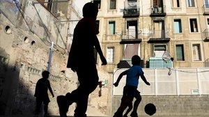 Varios niños juegana fútbolen una pista del Raval, en Barcelona.
