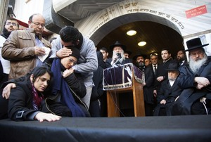 Family of victim of attack on a Paris grocery mourn beside a symbolic coffin during a procession near Tel Aviv