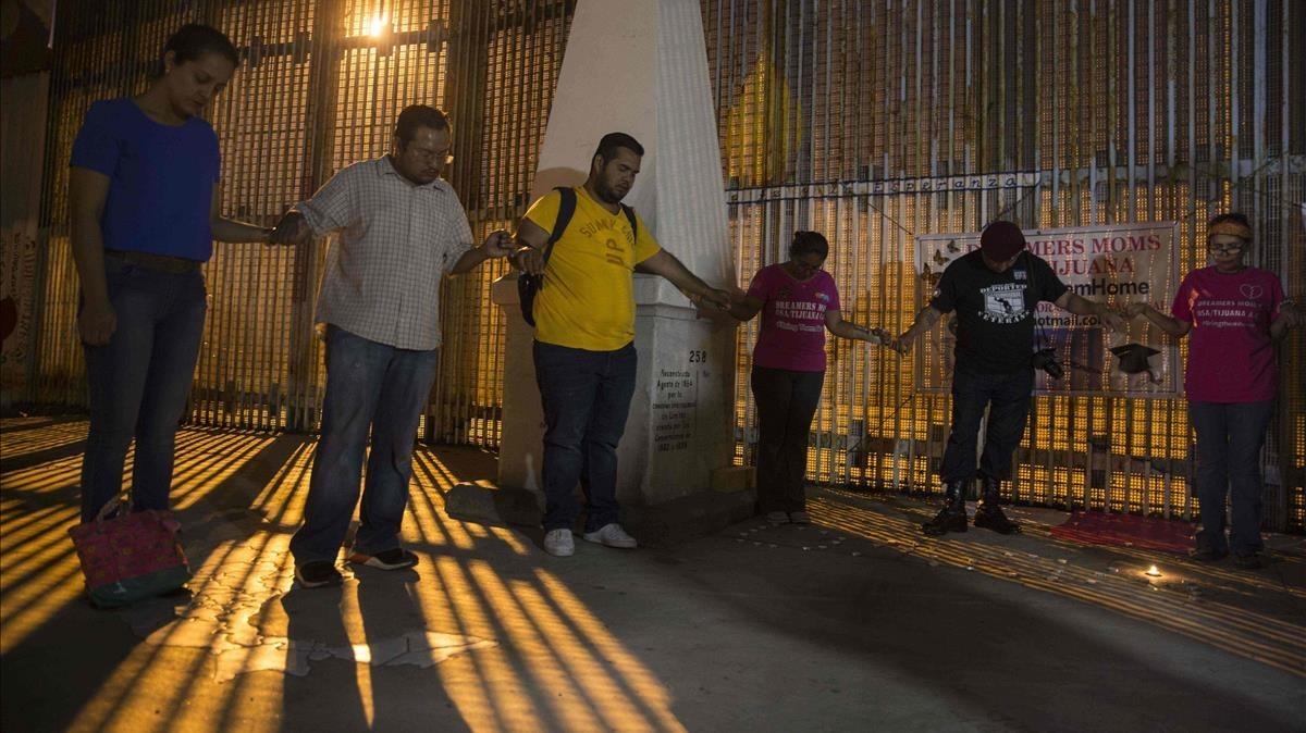 Activistas rezan junto al muro entre México y EEUU durante una protesta contra la posibilidad de deportación de dreamers, en Playas de Tijuana (Baja California, México), el 4 de septiembre.