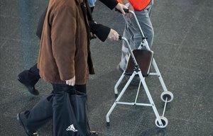 Un anciano se ayuda para caminar con un andador.
