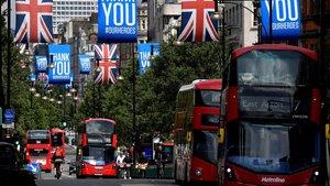 Autobuses pasan bajo banderas de la 'Union Jack' y pancartas con mensajes a los héroes del coronavirus en Oxford Street.
