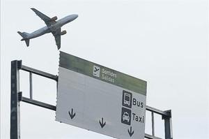 Un avión sobrevuela una de las señales de los accesos al aeropuerto de Barcelona.