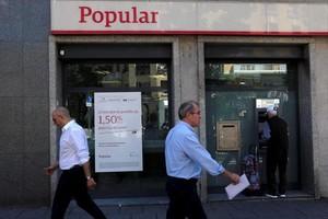 Un cliente usa un cajero automático en una oficina del Banco Popular en Madrid.
