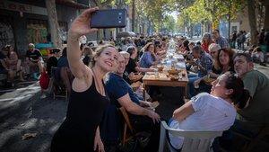 Vecinos del Poblenou degustan una paella popular con motivo de la reinaguración de La Flor de Maig, este sábado.