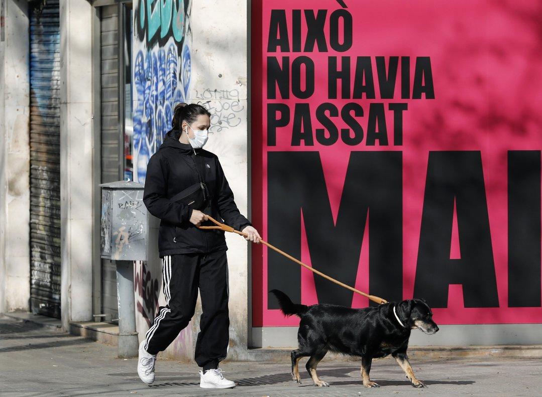 Una persona con mascarilla pasea alperro.