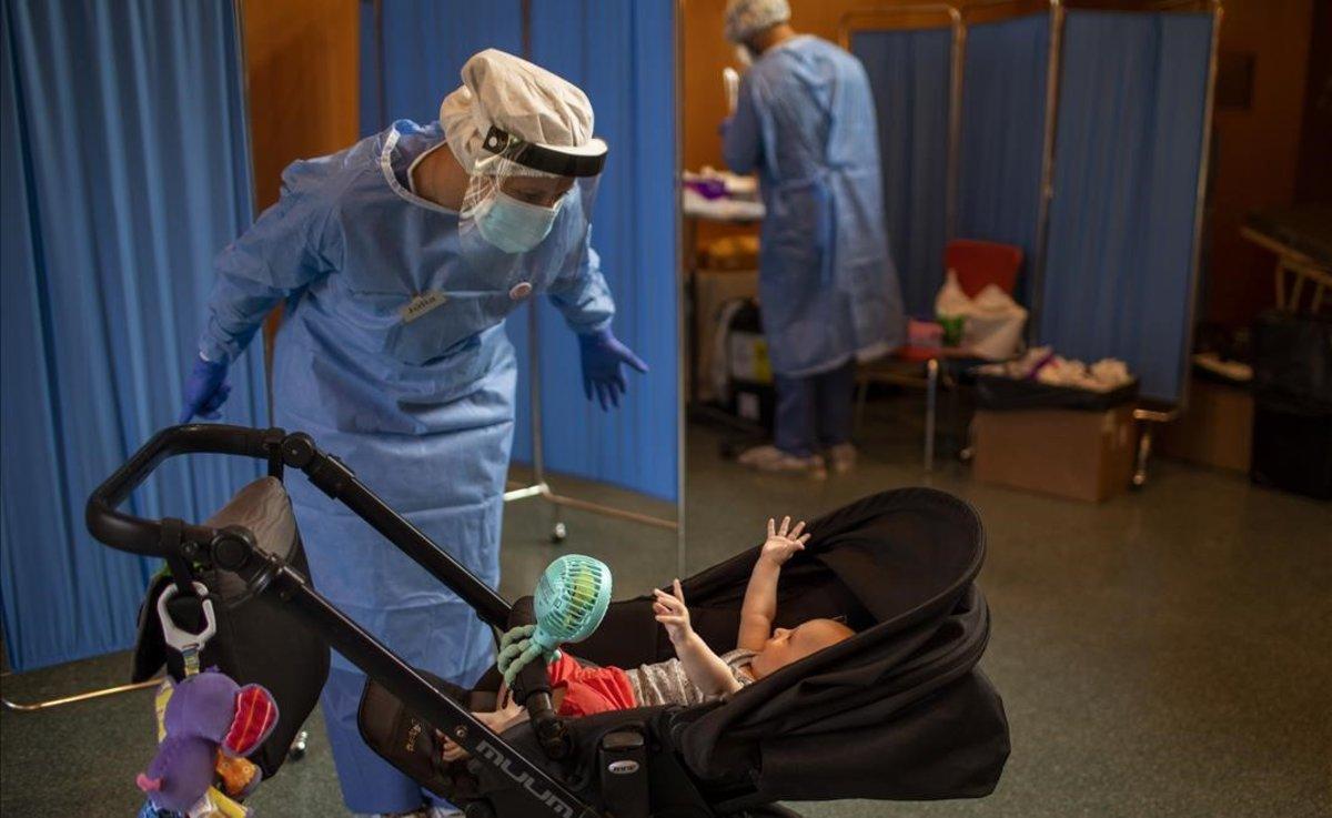 Una voluntaria de la ONG Open Arms juega con un niño de cuatro meses mientras espera a que su padre se haga un test PCR, en Vilafranca del Penedès.