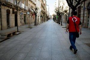 Un miembro de la Cruz Roja camina por una calle de Ourense (Galicia), vacía a causa del confinamiento por el coronavirus.