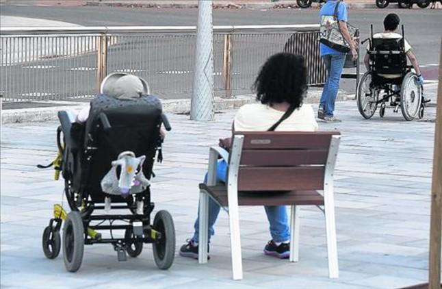 Dos personas dependientes, con sus cuidadores.