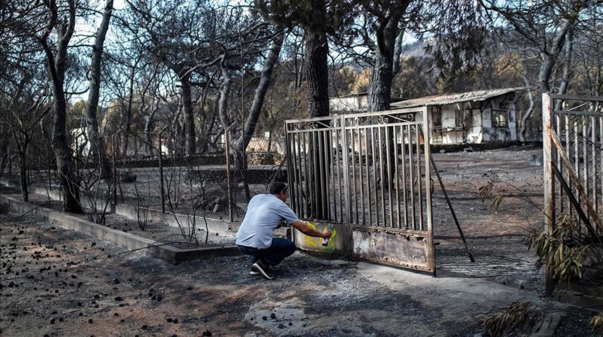 Un experto hace una marca en una casa quemada en Mati.