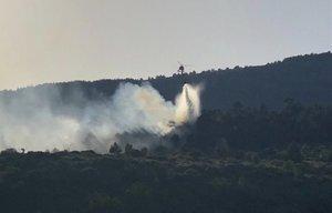 Un helicóptero arroja agua al foco del incendio forestal en la localidad de Robregordo.