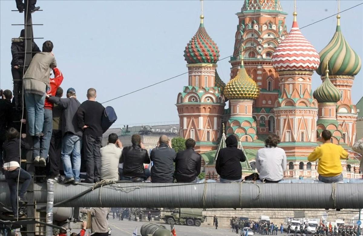 Un grupo de moscovitas observa el paso de varios misiles estrategicos Topol-M durante un desfile militar en la Plaza Roja de Moscu