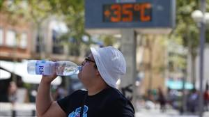 Un hombre se refresca ante un termómetro que marca 35 grados, en Barcelona.