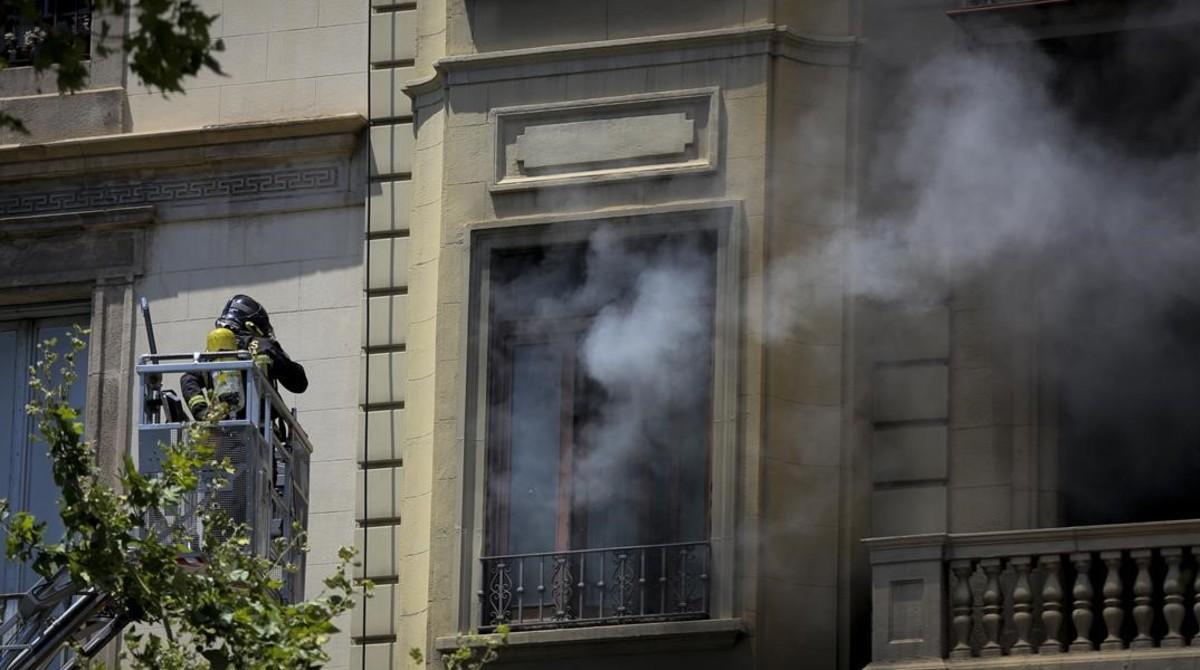 Un bombero trabaja en un incendio en un edificio de la Gran Via de Barcelona.