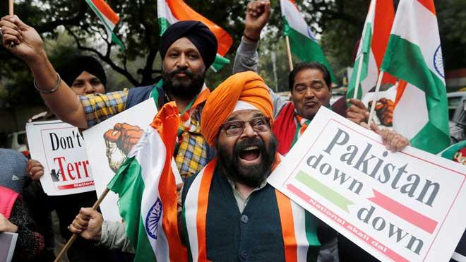 Un grupo de gente en Nueva Delhi celebra con banderas y pancartas la incursión militar en Pakistán.