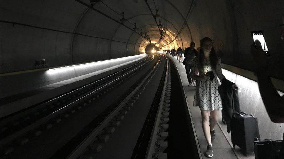 Instante en que decenas de pasajeros se bajaron del tren de Zurich, tras sufrir, hoy, una averia camino del aeropuerto.