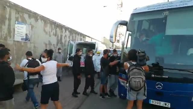 Los migrantes son trasladados en un autobús desde el muelle.