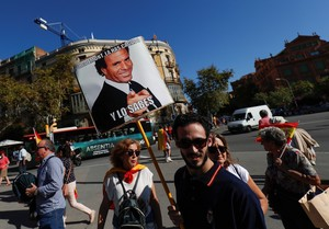 A man carries a sign depicting Spanish singer Julio Iglesias which reads Puigdemont you messed up and you know it as demonstrators gathered for a pro-union demonstration organised by the Catalan Civil Society organisation in Barcelona Spain October 8 2017 REUTERS Rafael Marchante
