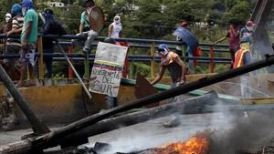 Manifestantes obstruyen una vía con una barricada en llamas, en Barquisimeto (Venezuela), el 26 de julio.