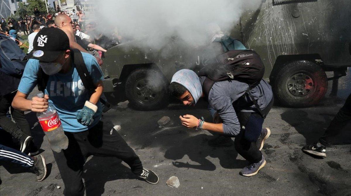 Manifestantes se refugian de los gases lacrimógenos en Santiago de Chile.