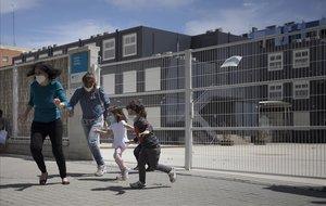 Niños con mascarilla juegan frente a la escula Flor de Maig, en el barrio de Poblenou, en Barcelona.