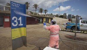 Operarios limpian las duchas y el mobiliario en la playa de la Mar Bella.