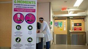 La responsable del centro de prevención y control de infecciones canadiense Adila Zahir se lava las manos en un hospital de Montreal, en Québec, junto a un panel informativo de cómo prevenir el contagio, este lunes.