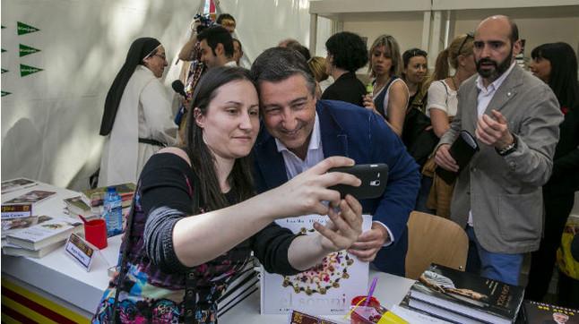 Una mujer se fotografía con el chef Joan Roca, que firma libros en Barcelona con motivo de la diada de Sant Jordi.