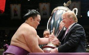 Trump recibe una copa de parte de un luchador de sumo, este domingo en Tokio.