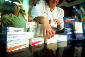 Una farmacéutica muestra medicamentos genéricos.