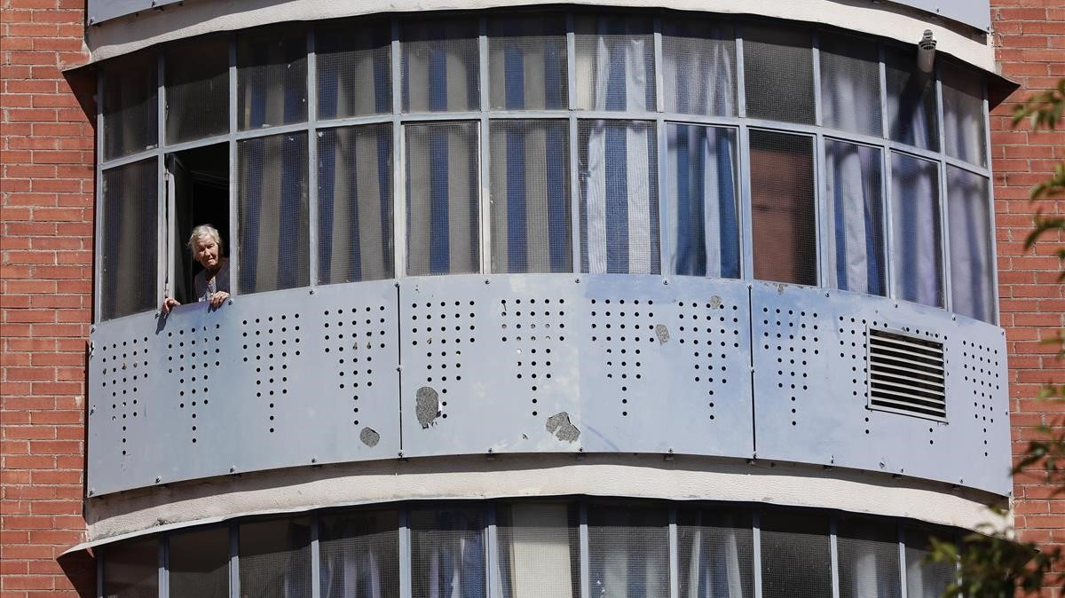 Una mujer se asoma a la ventana de su piso en Baró de Viver, esta semana.