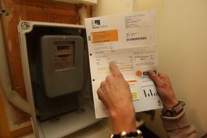 Una mujer consulta una factura de la luz frente al contador de su casa.