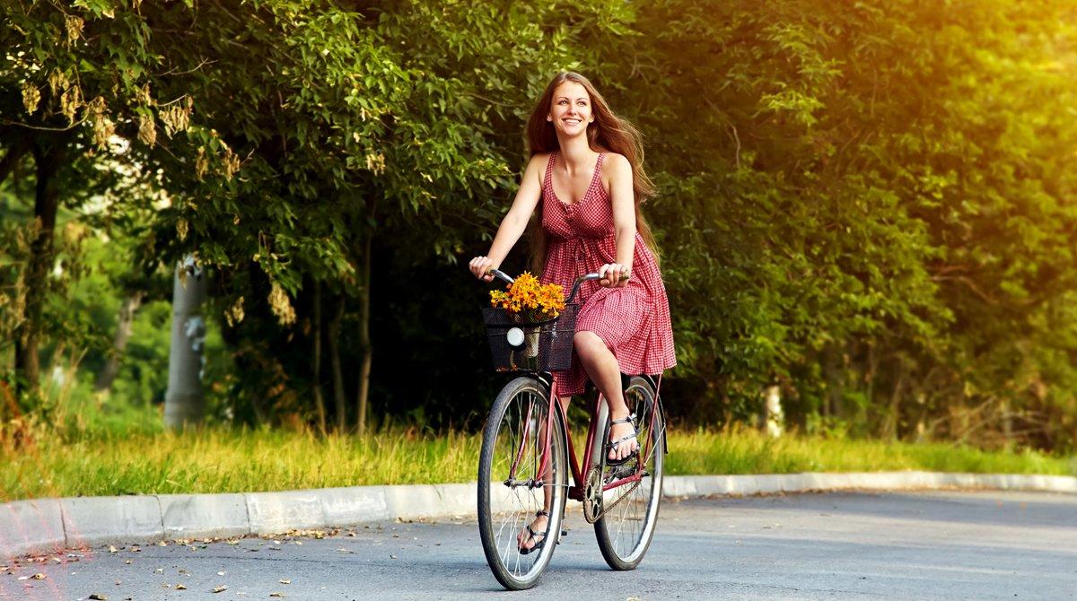 Una mujer pasea en bicicleta por el campo, en plena primavera.