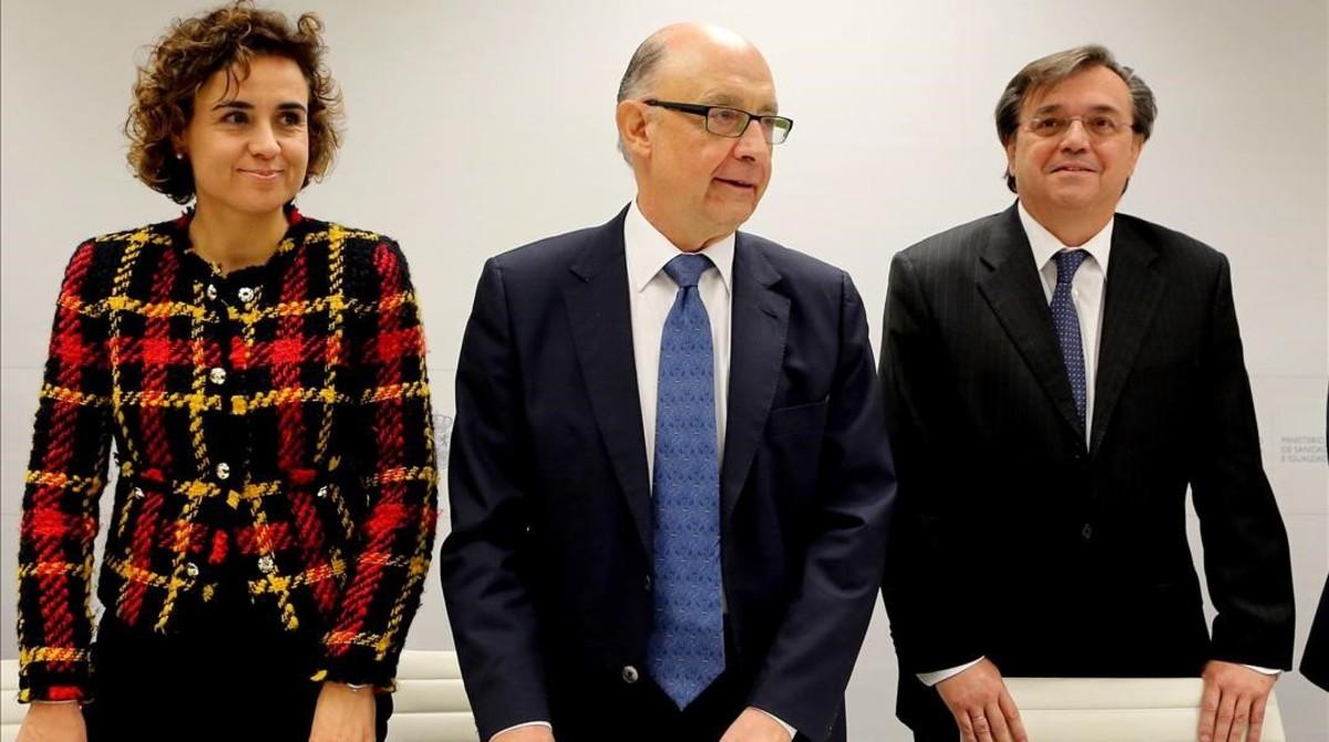 La ministra de Sanidad, Dolors Montserrat, el ministro de Hacienda, Cristobal Montoro, y el presidente de Farmaindustria,Jesus Acebillo, en el acto de renovación del convenio de control del gasto farmacéutico.