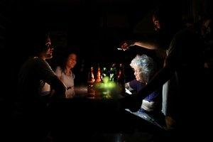 Personasen un bar en pleno apagón eléctrico en Venezuela.