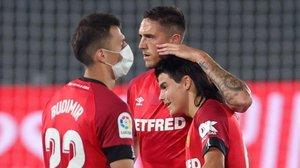 El veterano central Antonio Raíllo arropa, felicitándole, al jovencísimo Luka Romero, en su debut de anoche ante el Real Madrid, ante la mirada de Ante Budimir.