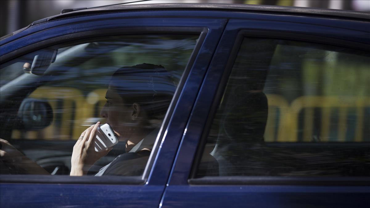 Una mujer utiliza el móvil mientras conduce.