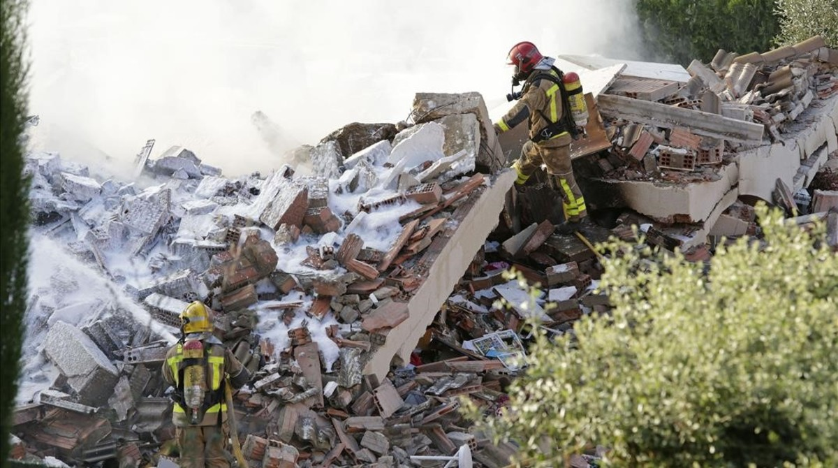 Los bomberos trabajan entre los escombros de la casa unifamiliar derrumbada tras una explosión en Collbató.