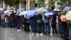 Cola de ciudadanos en Barcelona que se protegen de la lluvia con el paraguas / ARCHIVO.