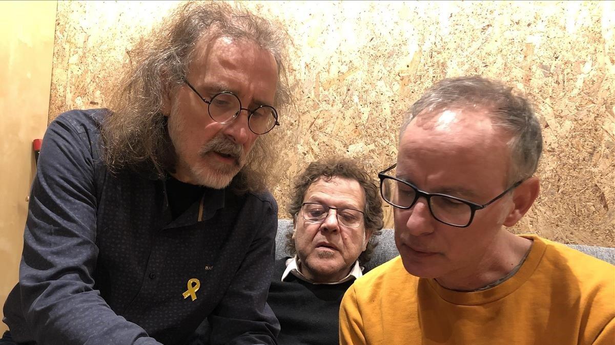 Joan Reig, Falin Cáceres y Lluís Gavaldà miran una foto en la que aparece el primero en una excursión del rector Llagostera.