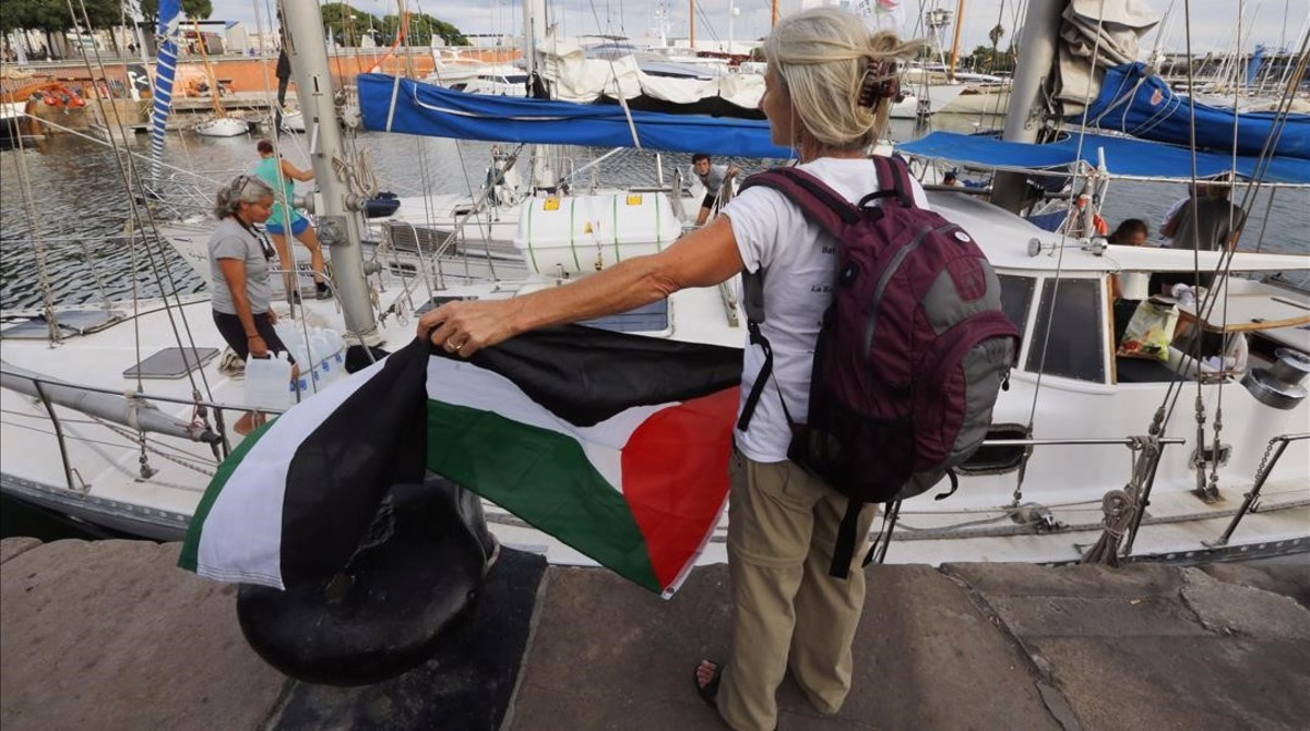 Una activista con la bandera palestina frente a uno de los dos veleros de la flotilla que ha partido hacia Gaza.