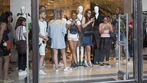 Unas personas se refugian dentro de un comercio en paseo de Gràcia.