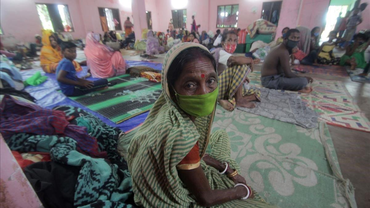 Personas evacuadas permanecen en el interior de un refugio a la espera de la llegada del ciclon Amphan a la bahia de Bengala, el pasado martes.
